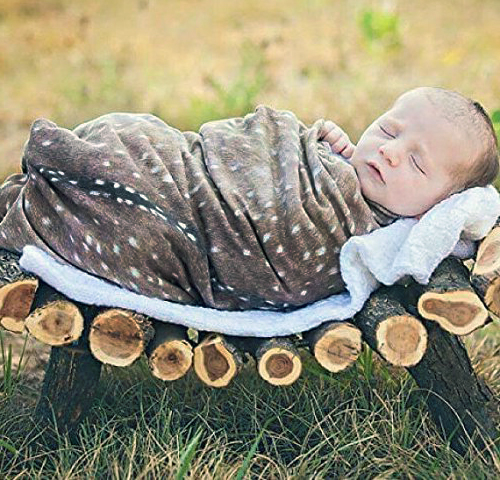 Woodland forest theme baby photo prop posing idea.  Newborn baby photo idea with deer skin and handmade log crib outside in fall.