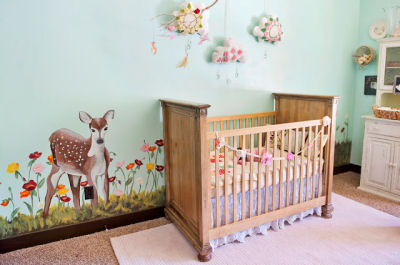 A fawn and forest creatures nursery wall mural in a baby girl deer theme nursery room
