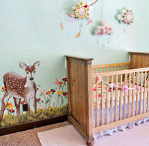 Nature themed baby girl nursery room with a deer wall mural