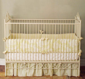 Yellow toile baby nursery bedding set in an antique off white crib