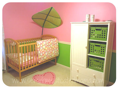 A white nursery armoire holds lime green storage bins