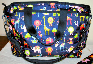 Satchel style baby diaper bag in navy blue with a zoo animals pattern