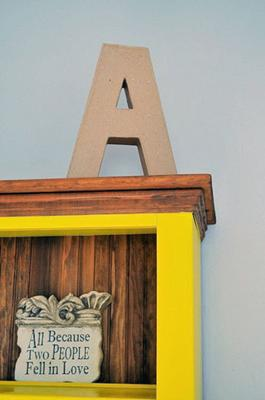 Asher's initial displayed on the bright yellow bookshelf made made with love by my step father in law, Gary